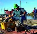 Trabalhador realizando obra próximo ao mangue